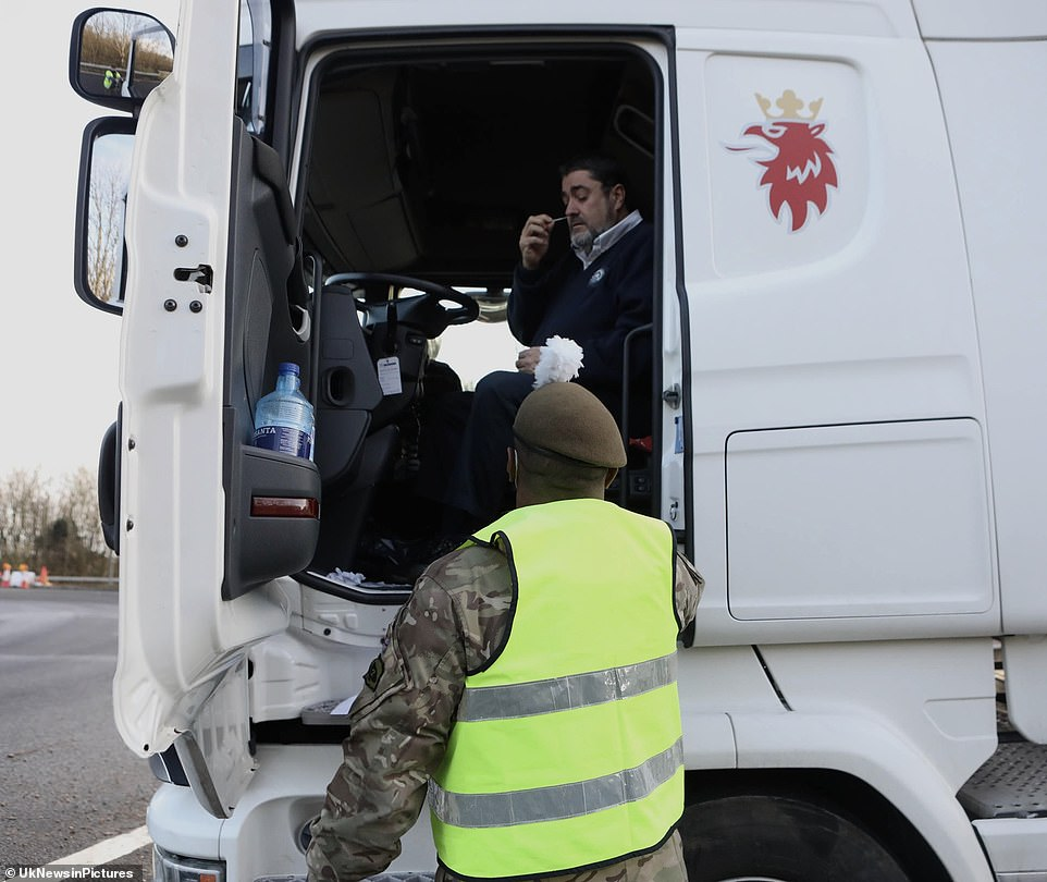A lorry driver self-administers a coronavirus test on Christmas Day as traffic begins to move slowly following tailbacks