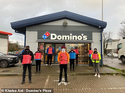 Sikh volunteers from Khalsa Aid and Domino's Pizza workers stand outside the branch in Sittingbourne, Kent, in preparation to deliver the fresh pizzas to stranded lorry drivers
