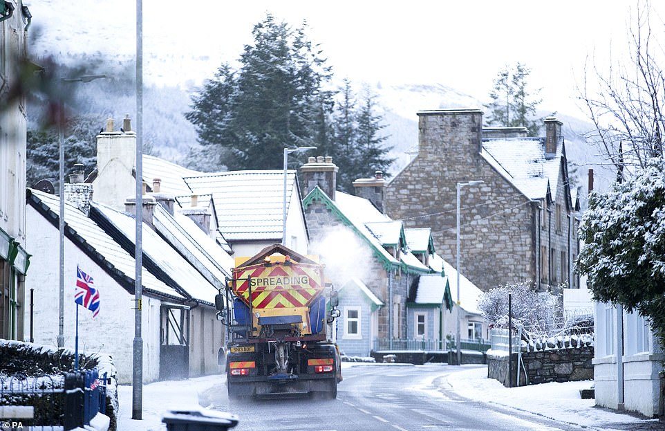 Snow plough spreads grit as it passes through Killin, Stirlingshire, where the Met Office has issued yellow weather warnings
