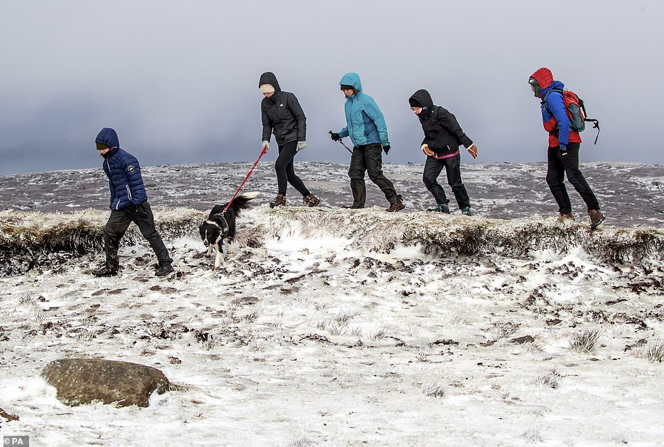 Hikers in snow on Bleaklow Moor in the Peak district of Derbyshire, after days of wet and wintry weather across the Christmas break