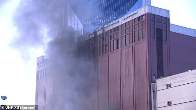 Smoke rises around the AT&T transmission center in downtown Nashville moments after the explosion on Friday morning