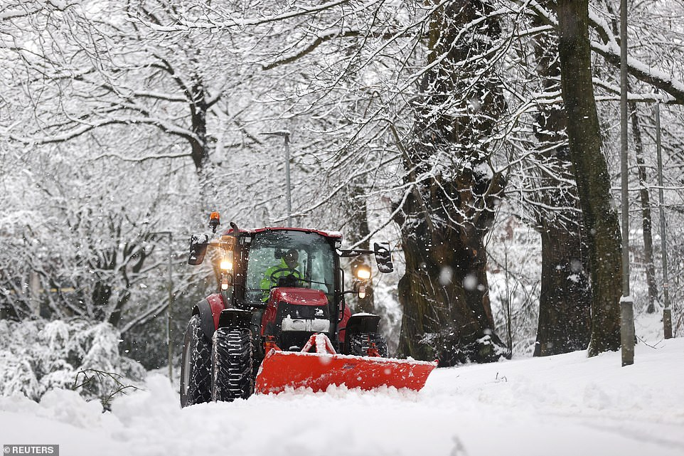 A snowplough drives down a road at Keele in Staffordshire yesterday as wintry weather hits parts of the West Midlands