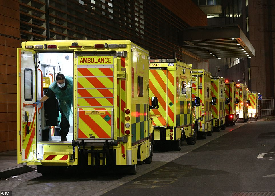 A paramedic wearing PPE is seen closing the door of the ambulance as the emergency vehicles queued outside the hospital
