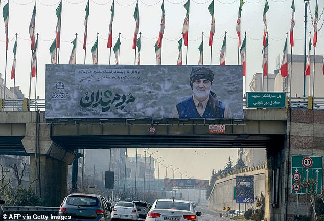 Iranians drive on a highway beneath a giant billboard depicting late Revolutionary Guards commander Qasem Soleimani, in the capital Tehran on Wednesday, ahead of the first anniversary of his killing in a US drone attack