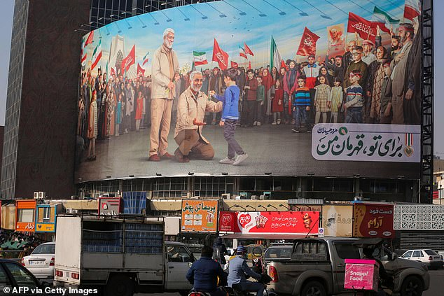 A giant billboard in Tehran on Wednesday depicting late Revolutionary Guards commander Qasem Soleimani (C) and top Iraqi commander Abu Mahdi al-Muhandis (C L)