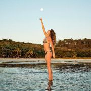 Gisele Bundchen basks in the glow of the full moon while wearing a bikini on the beach