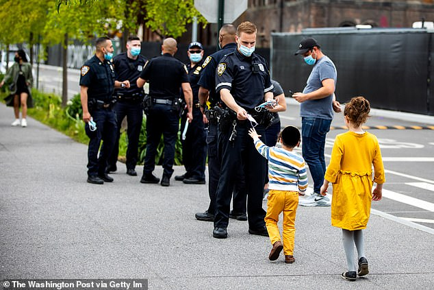 NYPD officers hand out mask at Domino Park in Williamsburg Brooklyn, New York, in May. The Health Department is now asking for volunteers to hand out masks in two upstate counties