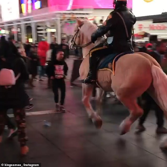 NYPD use police horses to break up fights in Times Square with the equines trampling over two men