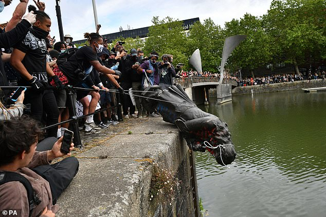 Pictured: People throwing a statue of Edward Colston into Bristol harbour during a Black Lives Matter protest rally in Bristol on June 7, 2020. Four people have since been charged with criminal damage over the toppling of the statue