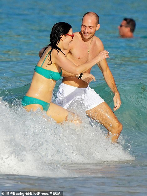 Rupert Murdoch's ex Wendi Deng, 52, frolics in the sea with hunky mystery man in St Barts