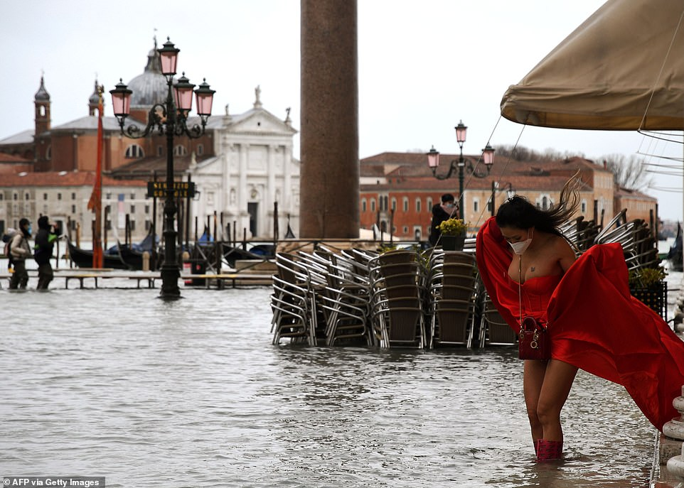 A woman in a red dress on a flooded St. Mark's Square on December 8, following following heavy rains and strong winds