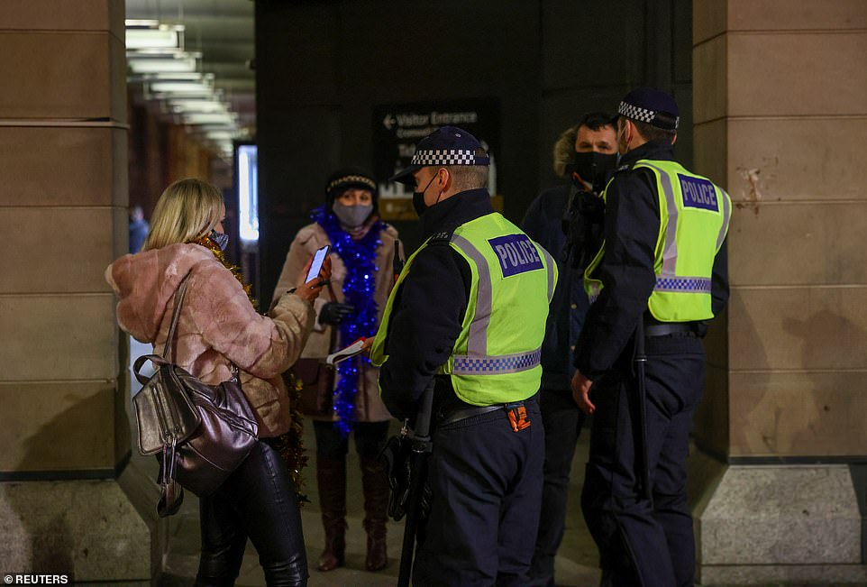 LONDON: Two police officers speak to a group of people this evening as Tier 4 restrictions mean New Year's Eve celebrations must be held in people's own homes rather than out partying