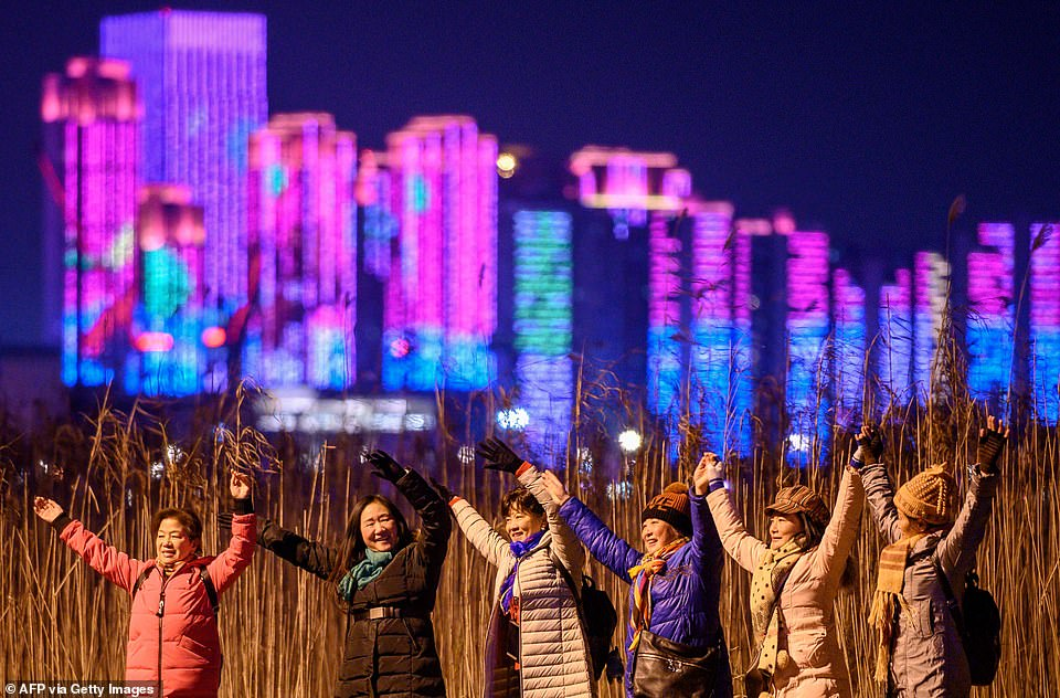 WUHAN:People pose for pictures on the banks of the Yangtze River on New Year's Eve in the city which became synonymous with the virus in the early weeks of the outbreak