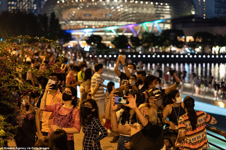 SINGAPORE: Crowds gathered in Singapore to welcome in the New Year. Many took photographs while wearing their protective face masks