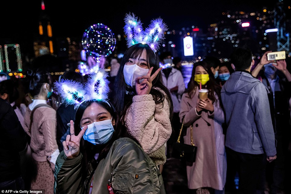 HONG KONG: Two women wearing light-up head bands pose for a photograph in Hong Kong as they bringin the new year