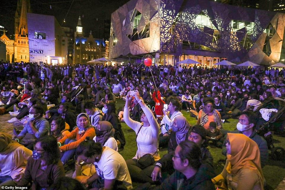 MELBOURNE: Vast crowds of people sat on the grass in Melbourne as they waited to welcome in the new year. Some wore masks while many others didn't