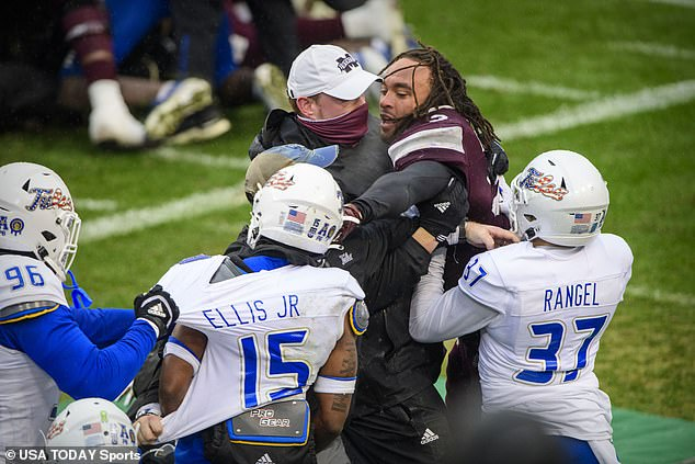 A trio of Tulsa players circle around a Mississippi State player, who is being restrained