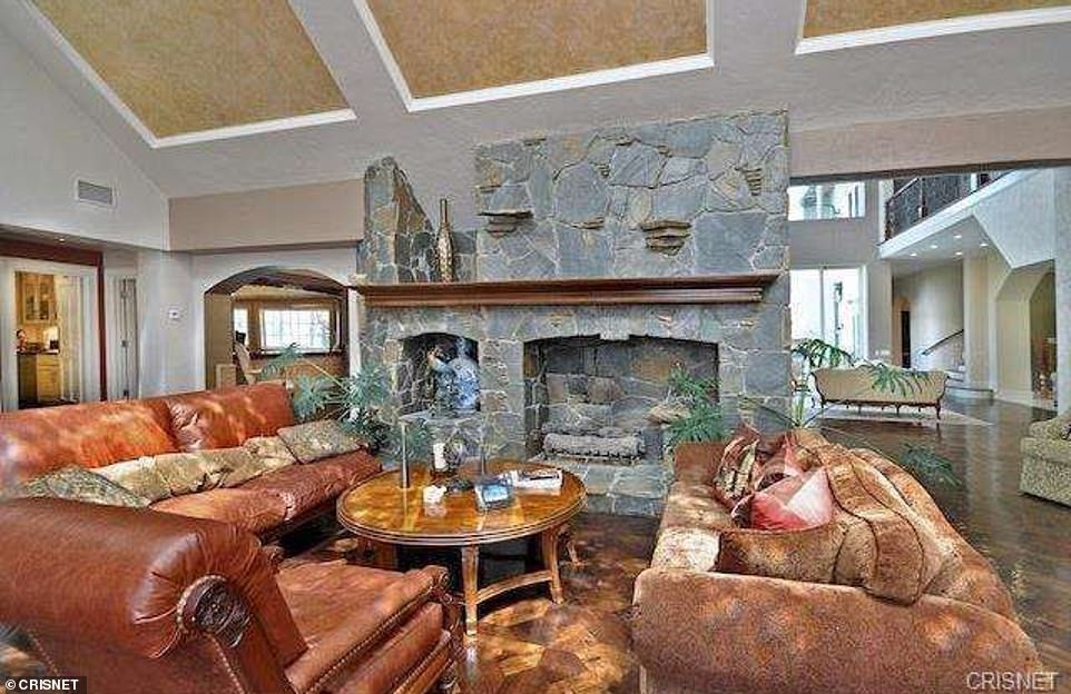 Living in the lap of luxury: This lavish 15,700-square-foot home built in 1989 is listed as the address for Grossman and her surgeon husband. A view of the home's posh living room with stone fireplace above