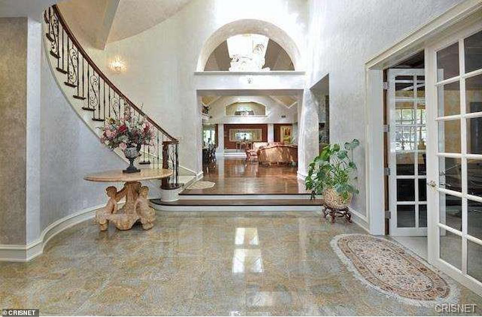 The nine-bedroom home's entry way and spiral staircase pictured above