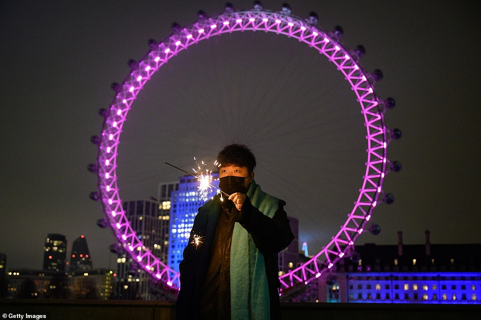 LONDON:A man holds a sparkler in front of the London Eye, in what would normally be a ticket-only area filled to capacity waiting for the annual fireworks display