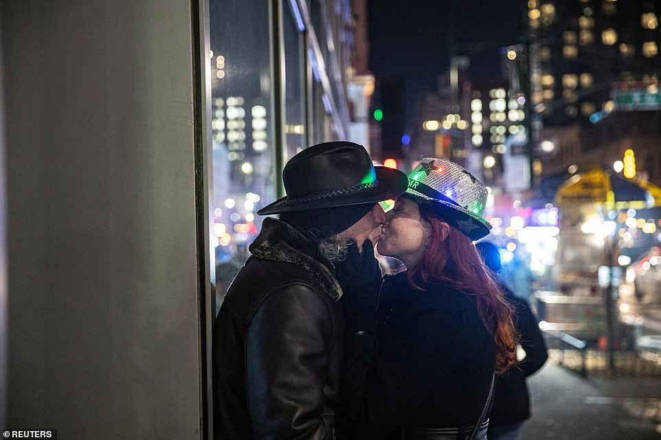 A couple kisses near Times Square during the virtual New Year's Eve event on Thursday