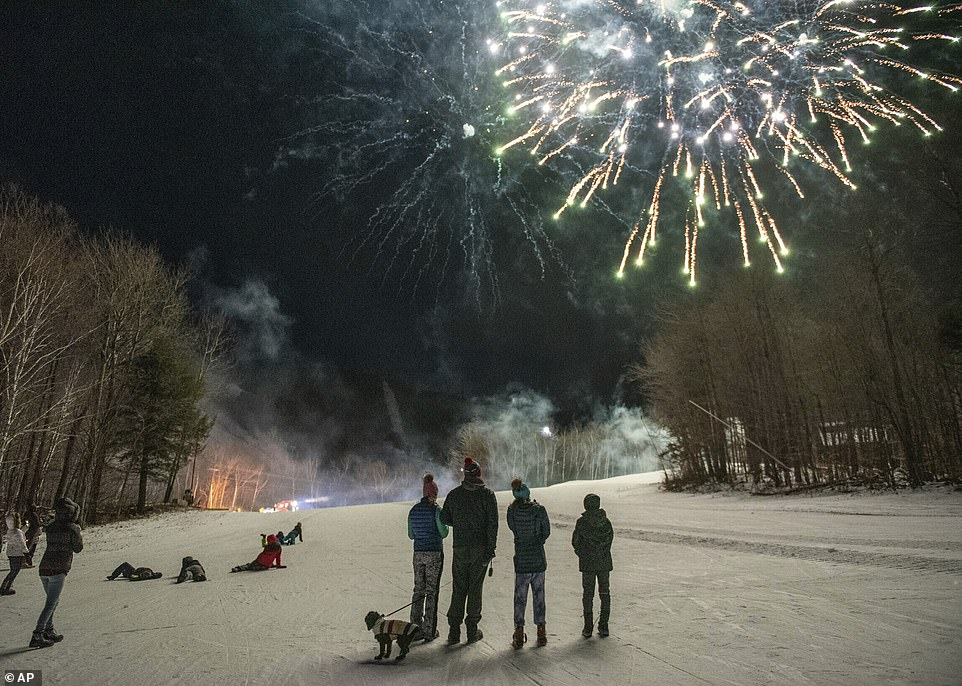 Sunday River guests watch the fireworks display on the side of the ski trails to ring in the New Year on Thursday in Newry, Maine. All festivities stopped promptly at 9pm in accordance with state guidelines