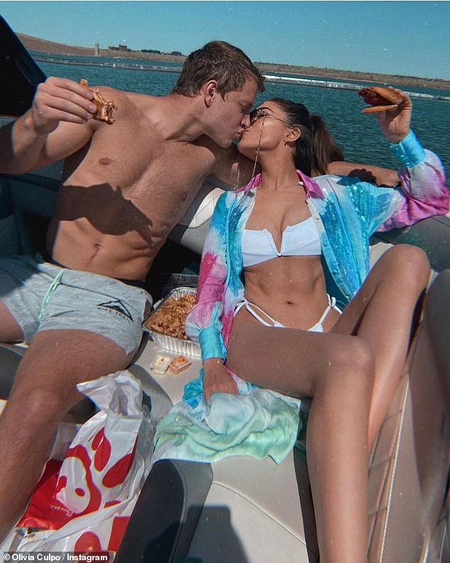 Happy New Year! Olivia Culpo ushered in 2021 with a kiss and fast food, posting a photo of herself and beau Christian McCaffrey chowing down on chicken sandwiches and smooching on board a yacht