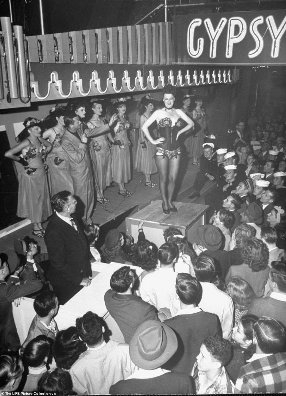 Gypsy Rose Lee told bawdy jokes with sharp comedic timing. Above, she laughs and soaks up cheers from the crowd imploring her to 'take it off.' The New York Times wrote: 'she eschewed the traditional crudities of burlesque.The burlesque entertainer was world-famous for her act, that included