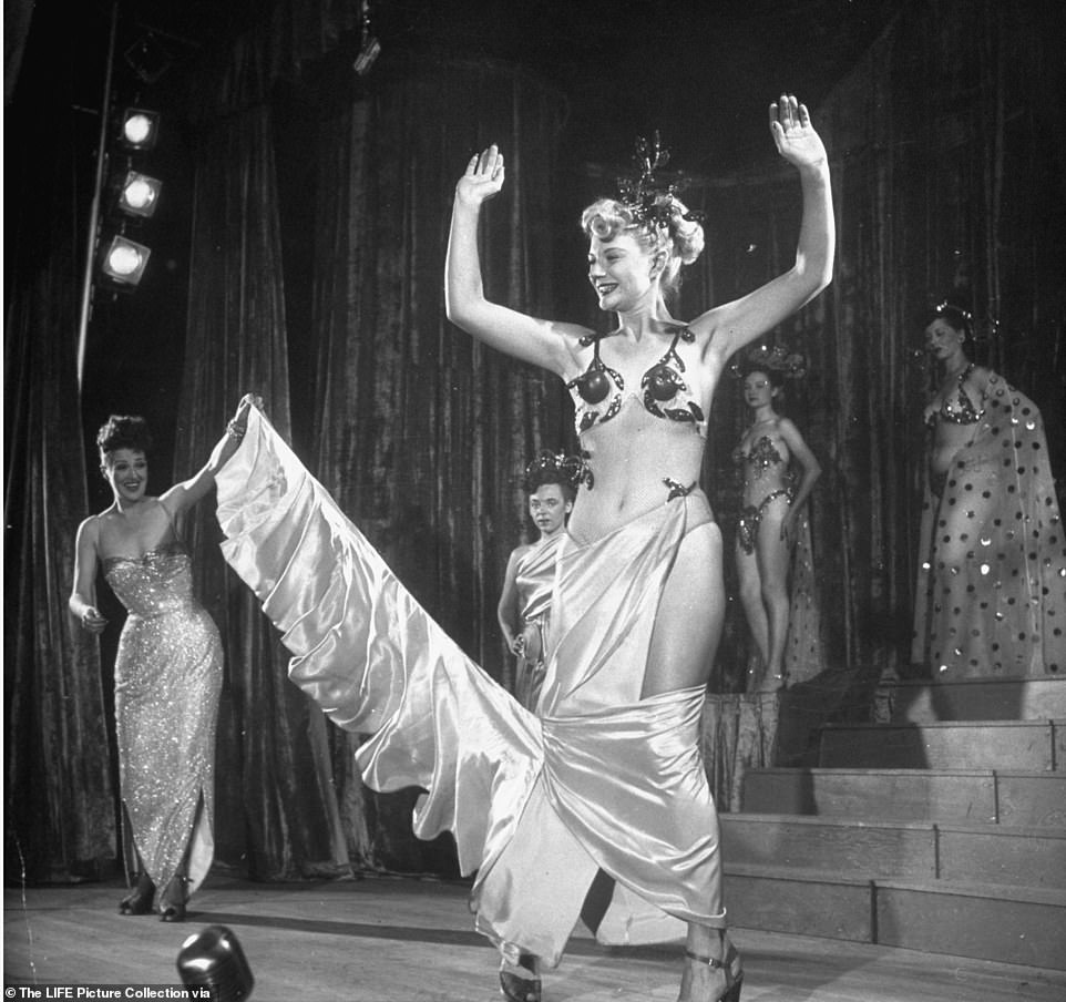 Burlesque dancer Gypsy Rose Lee (left) helps dancer Florence Bailey perform a reverse striptease act during Lee's carnival tour across the country.The finale of her show, according to the Tulsa World newspaper, was the story of Cinderella, with Lee as the Fairy Godmother, wearing a 97-pound dress containing over one million hand-sewn rhinestones