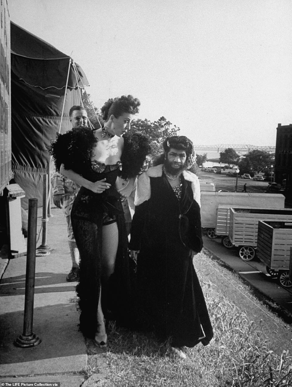 Gypsy Rose Lee walks the midway with friend and carnival freakshow star, the Bearded Lady Percilla Bejano, during her traveling carnival engagement across America