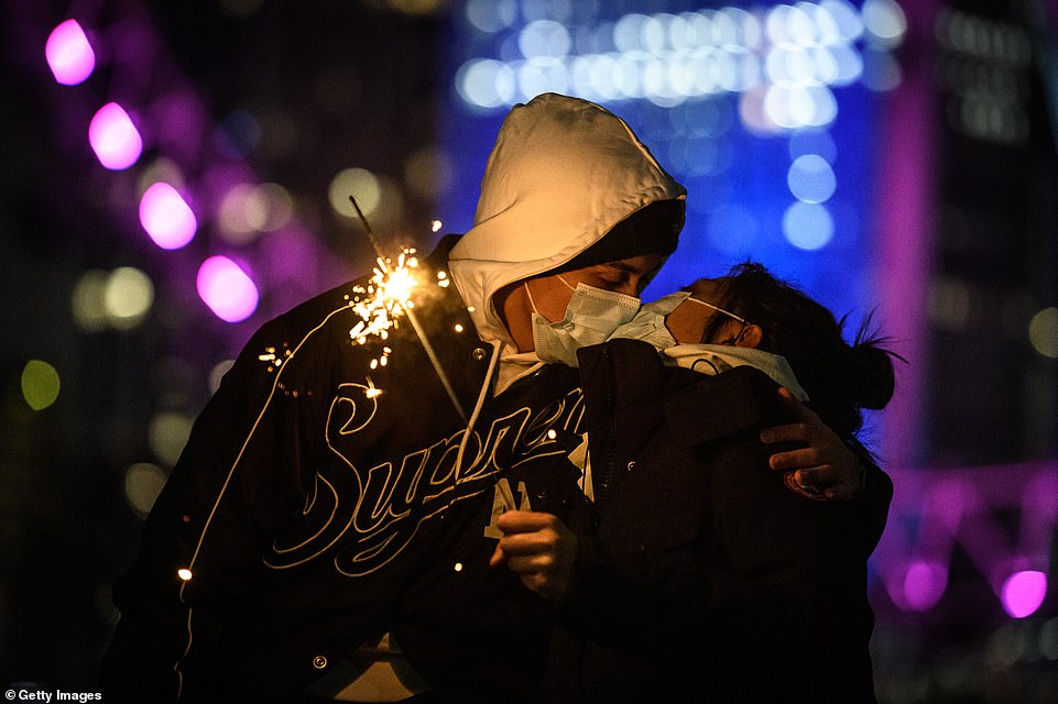 LONDON: A mask-wearing couple kiss while holding a sparkler in front of the London Eye. The annual firework display will not go ahead this year due to coronavirus