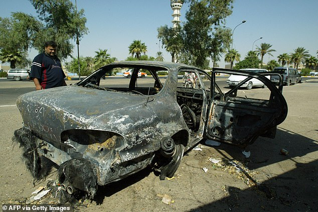 An Iraqi looks September 2007, at a burnt car on the site where Blackwater guards who were escorting US embassy officials opened fire in western Baghdad