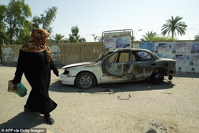 An Iraqi woman walks past a burnt car on the site where Blackwater guards who were escorting US embassy officials opened fire in the western Baghdad neighborhood of Yarmukh