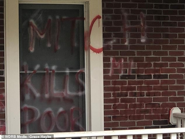 On the window adjacent to the front porch, graffiti is seen which says: 'MITCH KILLS THE POOR'
