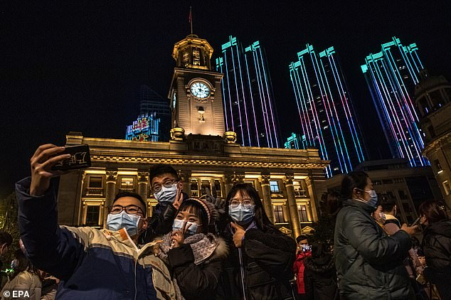 Revellers posed for a selfie in front of buildings lit up in bright colours. Wuhan had a more-normal New Year's Eve than many others across the globe