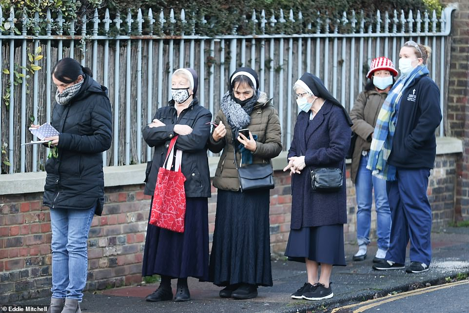 The rollout of the Pfizer/BioNTech vaccine began almost a month ago with more than a million people having already received their first coronavirus jab. Pictured: People queue to receive a Covid-19 vaccine at Sussex House in Brighton today