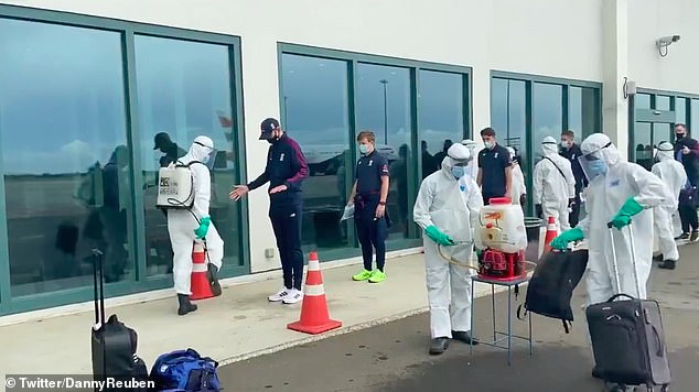 The players lined up to have their clothes disinfected by health officials outside the airport