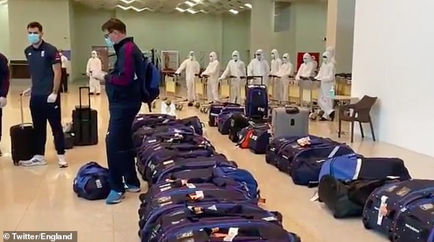 Officials in white hazmat suits line up ready to disinfect the touring party's luggage