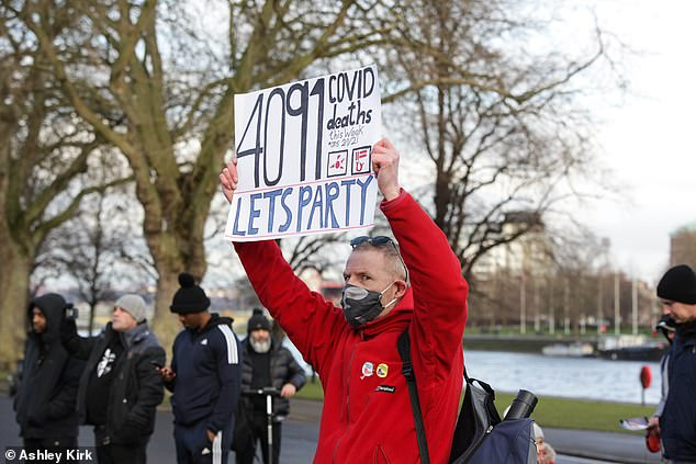 Yesterday Britain confirmed it had suffered 4091 Covid-19 deaths in a week, demonstrators held up placards with the figure, adding: 'Let's party'
