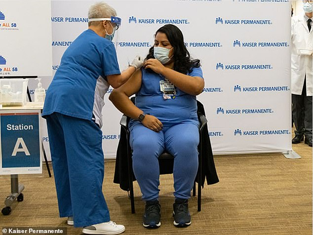 The emergency staff were the first to receive the COVID-19 vaccine less than 10 days ago, but the hospital said they 'would not be expected to have reached immunity when this exposure occurred.' A view of a Kaiser Permanente staffer getting vaccinated on December 14 above