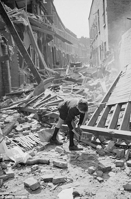 A boy retrieves an item from a rubble-strewn street after German bombing raids in the first month of the Blitz, September 1940