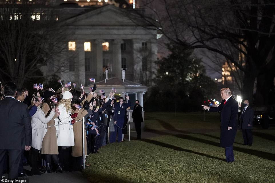 Trump greeted supporters on the lawn who waved American flags on the South Lawn Monday night