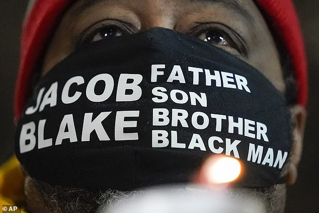Jacob Blake Sr., father of Jacob Blake, holds a candle at a rally Monday, January 4, in Kenosha, Wisconsin