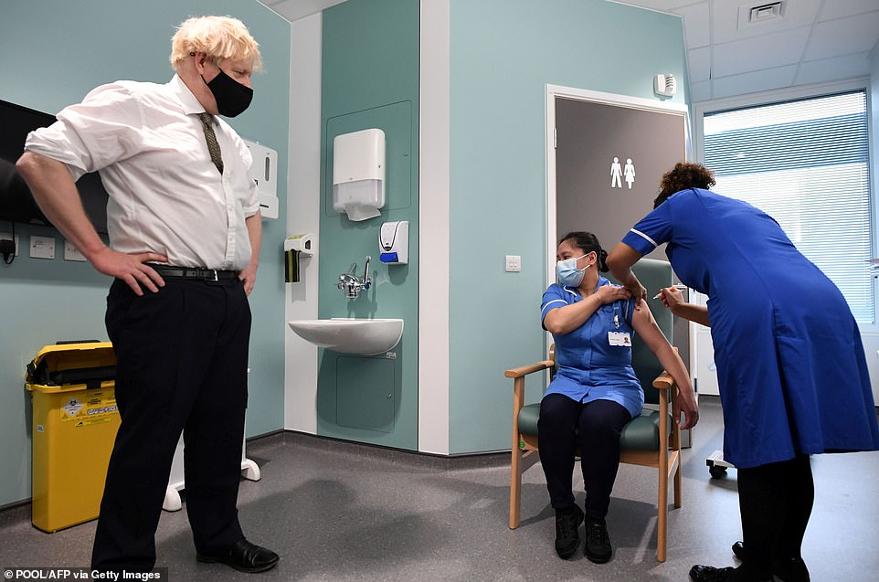 Britain's Prime Minister Boris Johnson watches as Jennifer Dumasi receives a dose of the AstraZeneca/Oxford Covid-19 vaccine during a visit to Chase Farm Hospital in north London