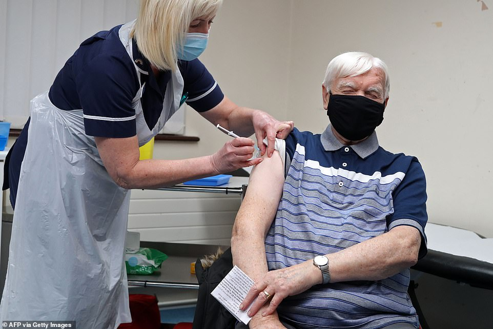 Practice Sister Tina Sutton (left) administers a dose of the AstraZeneca/Oxford Covid-19 vaccine to Derek Davies Games at the Pontcae Medical Practice in Merthyr Tydfil in Wales