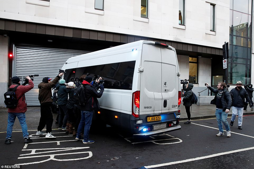 A prison van arrives at the Westminster Magistrates Court this morning ahead of Assange's bail application hearing, as photographers try to picture Assange inside