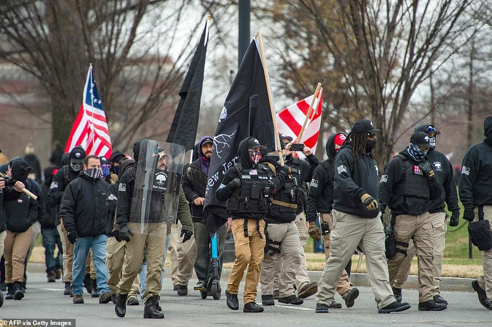 A militia-like group is seen making their way to Trump's rally on Wednesday morning
