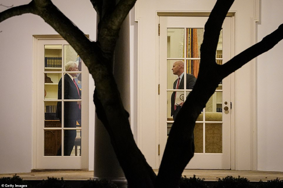 Vice President Mike Pence (left) and his Chief of Staff Marc Short stand in the Oval Office before President Donald Trump departs the White House on Monday for a campaign rally in Georgia