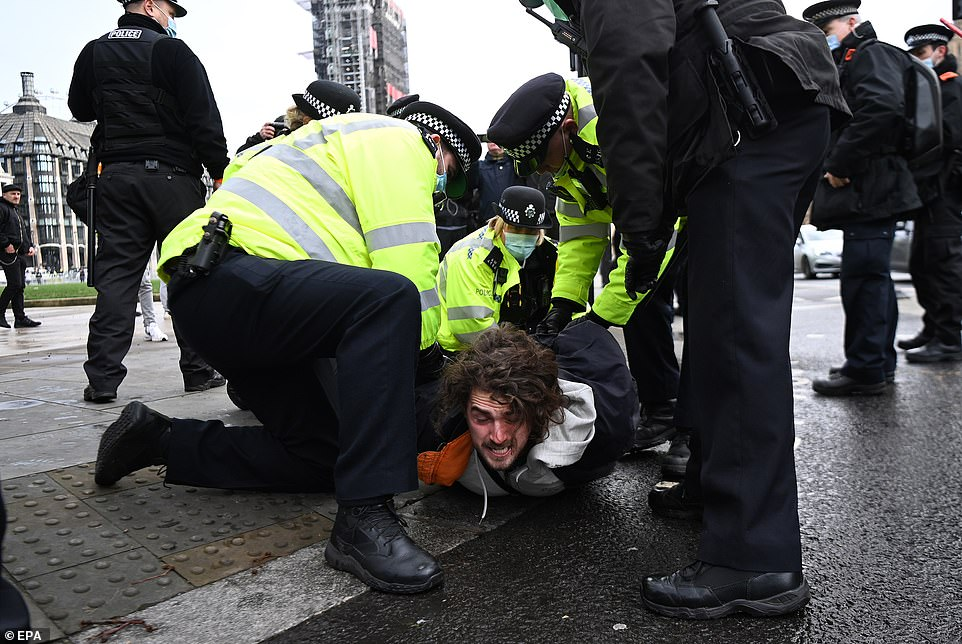 Five officers, several armed with batons, broke up the protest outside the Houses of Parliament, pinning this man to the ground