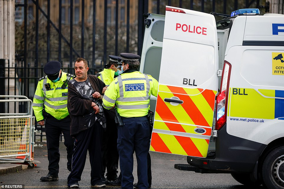 Police officers detain a demonstrator at Parliament Square during an anti-lockdown protest that breached Covid lockdown rules